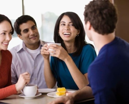 Spanish lessons in NYC. Friends talking in cafe in New York, NY, speaking Spanish