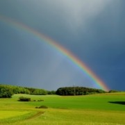 A picture of a pasture in upstate new york after a thunderstorm with a rainbow in the sky, this image is used to teach about the weather in Spanish language instruction NYC